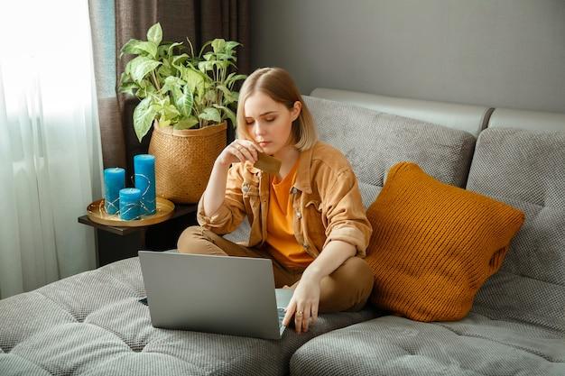 Bella giovane donna acquirente effettua acquisti online utilizzando laptop e carte di debito di credito mentre è seduto sul divano di casa. la donna fa acquisti online premurosamente. compratore premuroso dubbioso