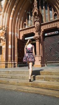 Bella giovane donna in abito corto in piedi su vecchie scale di pietra nella cattedrale cattolica di città europea european