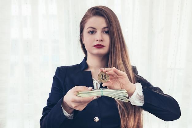 Bella giovane donna che mostra bitcoin e banconote in dollari