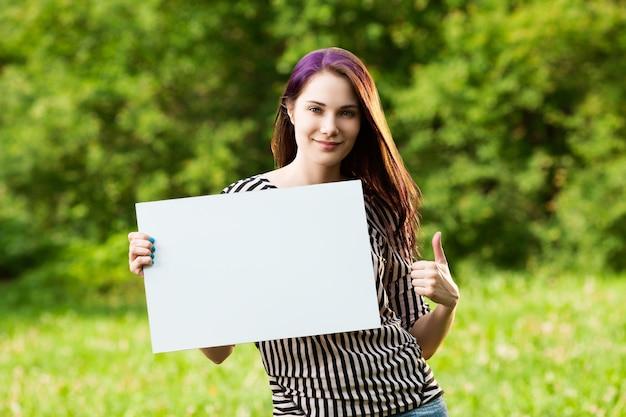 Bella giovane donna che mostra un bordo bianco in bianco e un pollice in su