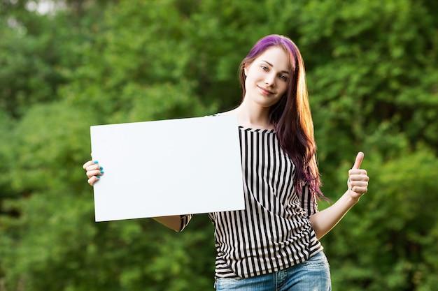 Bella giovane donna che mostra un manifesto bianco in bianco e un pollice in su