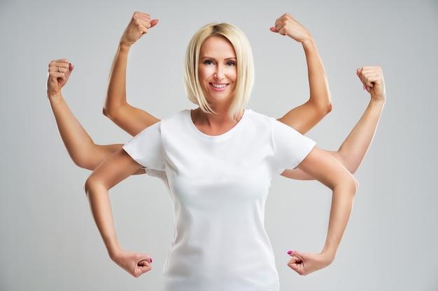 Bella giovane donna che mostra la sua muscolosità e guarda la telecamera