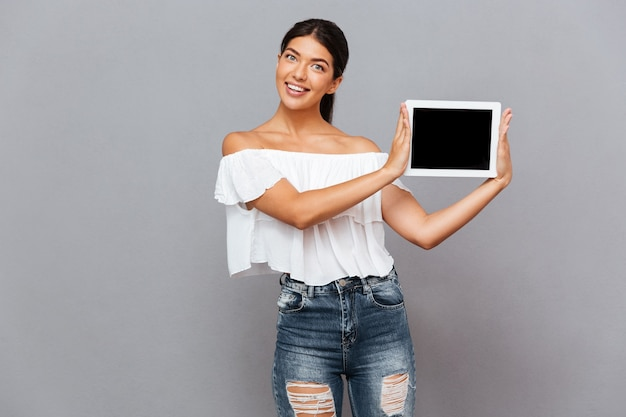 Bella giovane donna che mostra computer tablet con schermo vuoto isolato su un muro grigio