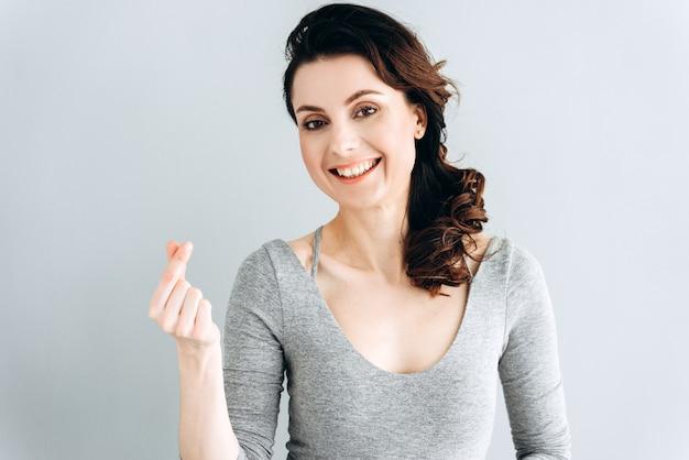 Bella, giovane donna mostra un gesto di denaro, paga lo stipendio.