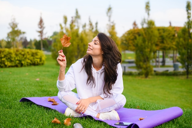 La bella giovane donna si siede al tappeto viola sportivo nel parco autunnale della città, prende e guarda una foglia secca dopo l'allenamento all'aperto