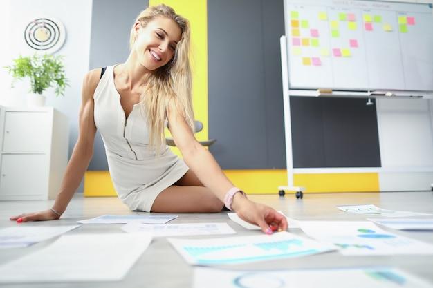 La bella giovane donna si siede sul pavimento nell'ufficio e raccoglie i documenti bionda felice