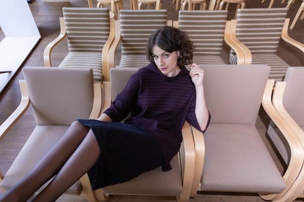 Bella giovane donna seduta da sola nella fila di sedie in auditorium.