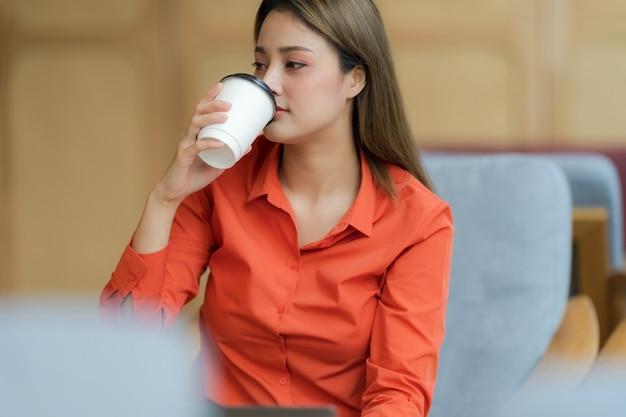 Bella giovane donna seduta in una caffetteria con bere caffè