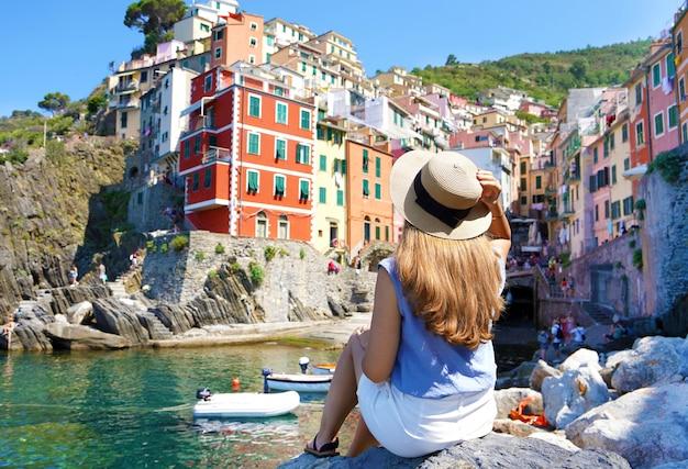 Bella giovane donna seduta su roccia godendo di una fantastica vista del colorato villaggio di riomaggiore nelle cinque terre, italy