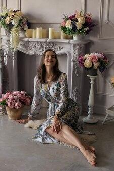 Bella giovane donna seduta in una stanza tra i fiori