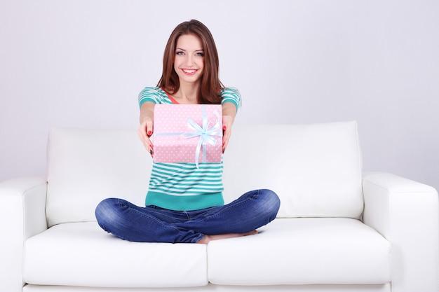 Bella giovane donna seduta sul divano con confezione regalo su sfondo grigio