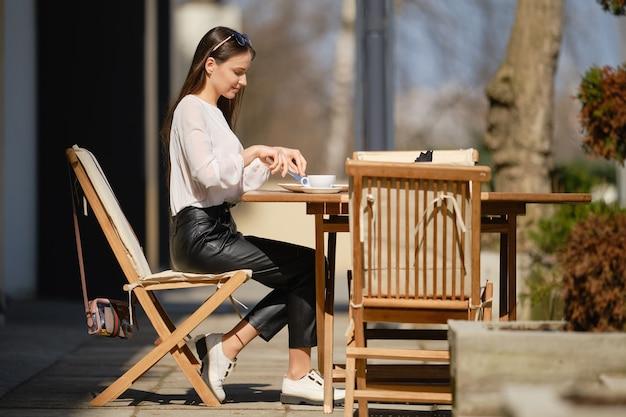 Bella giovane donna seduta sulla terrazza del caffè in una giornata di sole e mangiare la torta. donna che gode del primo sole primaverile all'aperto.