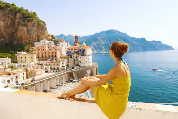 Bella giovane donna seduta sul muro guardando lo splendido villaggio panoramico di atrani sulla costiera amalfitana, italia