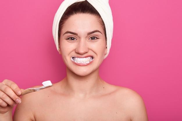 La bella giovane donna sorride ampiamente, lavandosi i denti e guardando la fotocamera con felice espressione facciale, in posa con un asciugamano