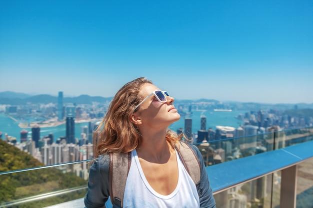 La bella giovane donna sorride felicemente e mette il suo viso al sole