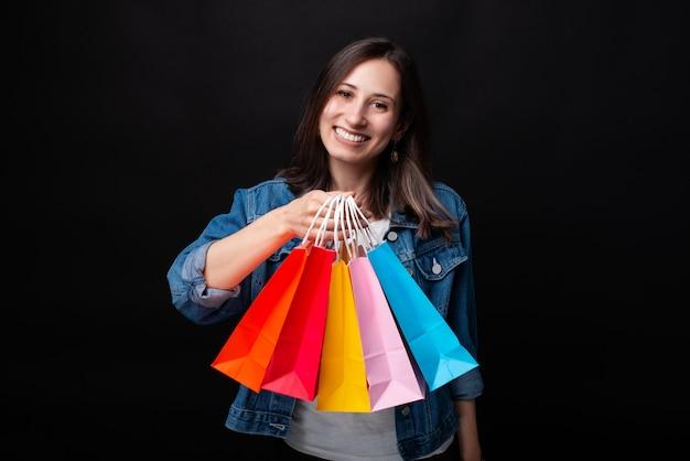 Bella giovane donna che sorride alla macchina fotografica che mostra i suoi sacchi di carta variopinti di acquisto su fondo nero.