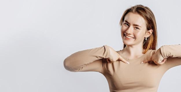 Bella giovane donna sorridente e puntando le dita su se stessa su un muro bianco isolato