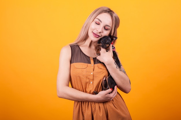 Bella giovane donna che sorride e che mostra affetto per il suo piccolo cucciolo su sfondo giallo. vestito casual. amante dei cani.