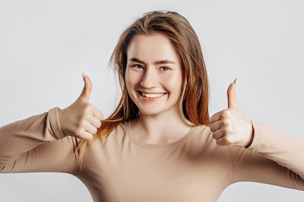 La bella giovane donna che sorride e mostra i pollici aumenta il gesto con due mani su una parete isolata bianca