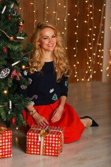 Bella giovane donna sorridente e seduta sul pavimento vicino all'albero di natale in interni decorati per natale