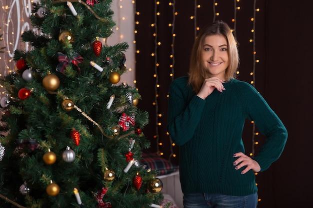 La bella giovane donna che sorride e sta vicino all'albero di natale.