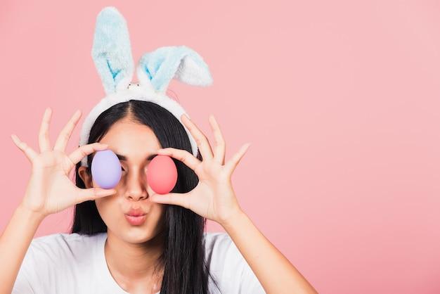Bella giovane donna sorridente che indossa le orecchie di coniglio che tengono gli occhi colorati anteriori delle uova di pasqua