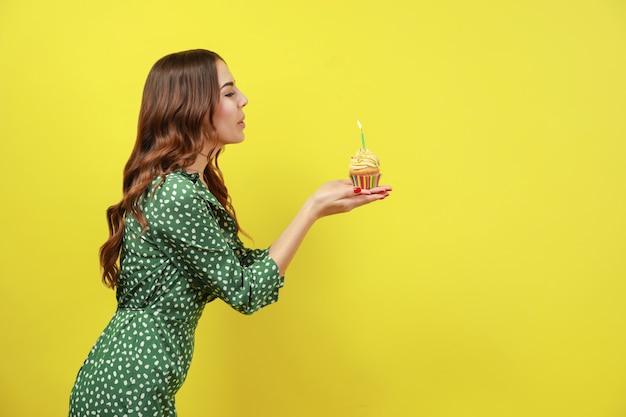 Bella giovane donna che spegne la candela sul bigné di compleanno contro il colore di sfondo