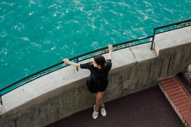 Bella giovane donna in piedi su una spiaggia azzurra in un abito nero.
