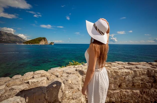 Bella giovane donna in piedi sulla riva del mare in alto e guardando l'isola in mare