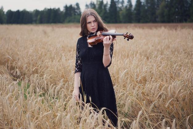 Una bellissima giovane donna in piedi in un campo di grano suonerà il violino