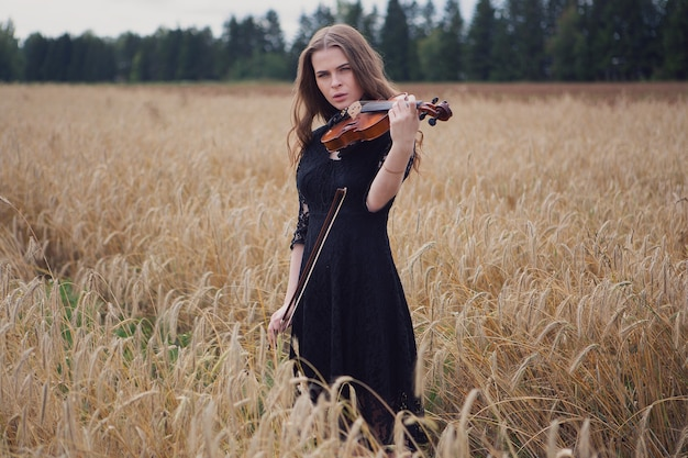 Bella giovane donna in piedi sul campo di grano suona il violino