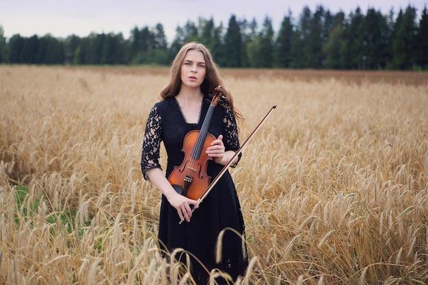 Bella giovane donna in piedi su un campo di grano preme un violino
