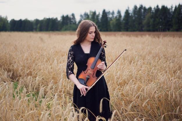 Bella giovane donna in piedi su un campo di grano con violino