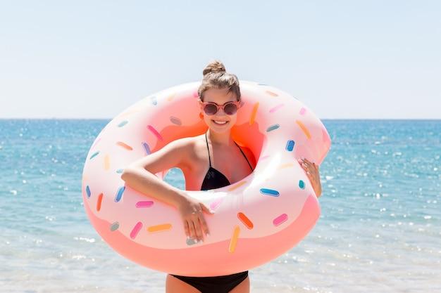 La bella giovane donna resta sulla spiaggia del mare con la ciambella gonfiabile dell'anello e si diverte. vacanze estive e concetto di vacanza.