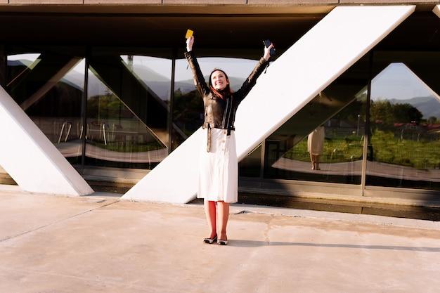 Bella giovane donna per strada nella zona commerciale con le braccia alzate con smartphone e carta di credito sorridenti contenti. concetto di acquisto su internet