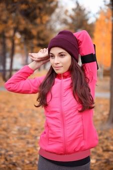Bella giovane donna che si estende nel parco autunnale