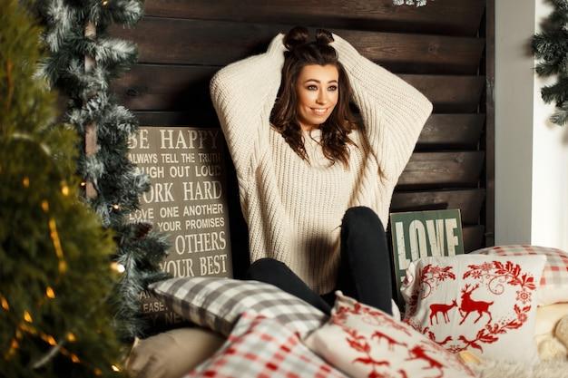 Bella giovane donna in un maglione lavorato a maglia alla moda sul letto