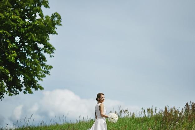 Bella giovane donna in un vestito bianco alla moda con pettinatura di nozze che tiene un mazzo dei fiori bianchi e che posa all'aperto in un campo verde