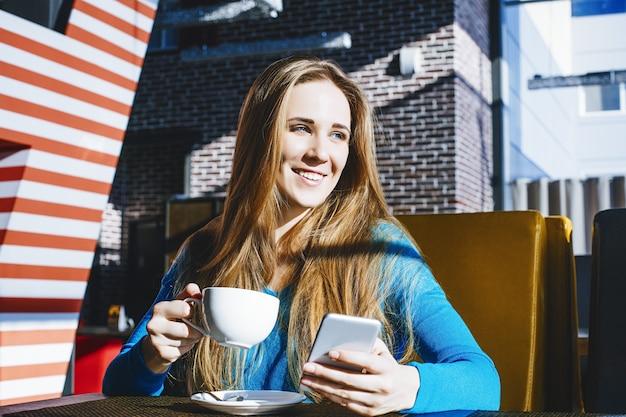 Bella giovane donna moda di successo e bella con un telefono cellulare e una tazza di caffè in un bar