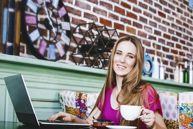 Moda di successo di bella giovane donna e belle opere su un computer portatile al tavolo con una tazza di caffè