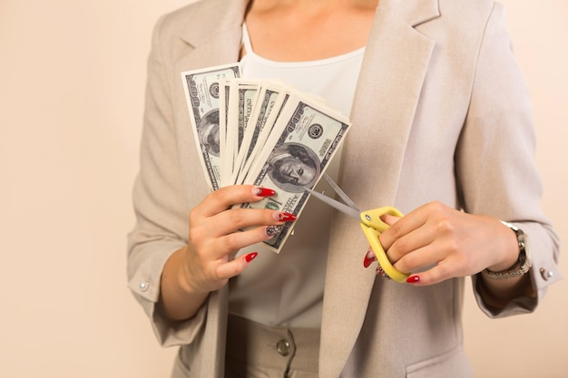 Bella giovane donna in un vestito su beige taglia i dollari con le forbici