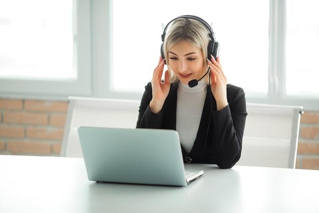 Bella giovane donna in un vestito in ufficio al tavolo con un computer portatile in cuffia
