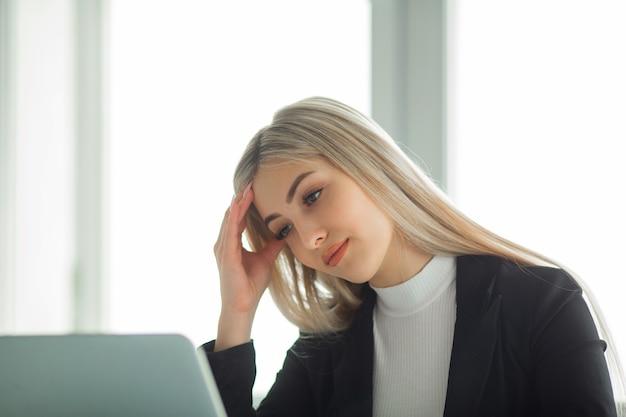 Bella giovane donna in un vestito in ufficio al tavolo con un computer portatile
