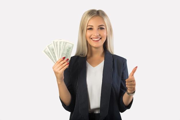 Bella giovane donna in un vestito su uno sfondo bianco con dollari in mano con un gesto della mano