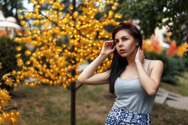 Bella giovane donna in abiti estivi vicino a un albero con luci