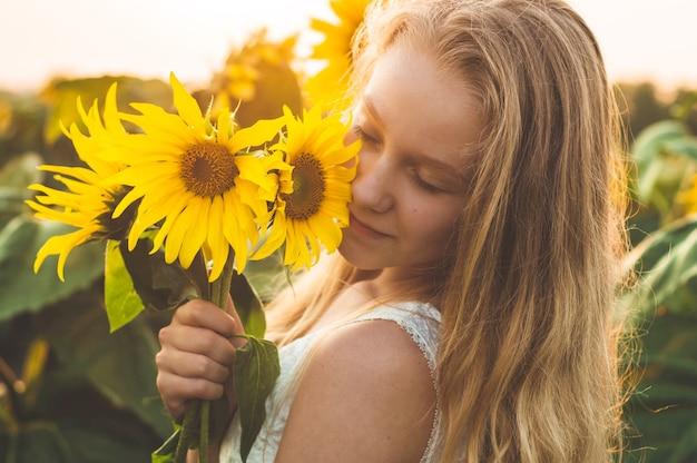Bella giovane donna in un campo di girasoli. ritratto di una giovane donna al sole. concetto di allergie ai pollini. felicità dello stile di vita all'aperto