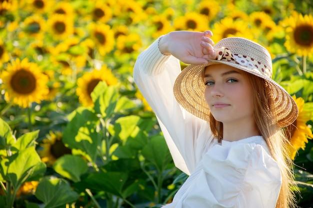 Bella giovane donna in un campo di girasoli con un cappello di paglia