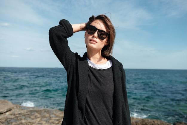 Bella giovane donna in occhiali da sole in piedi in riva al mare