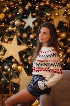 Una bella giovane donna con un maglione è seduta in attesa di una vacanza vicino all'albero di capodanno decorato con ghirlande dorate e decorazioni natalizie. l'idea e il concetto di natale e capodanno