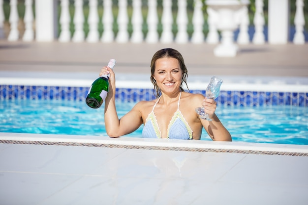 Bella giovane donna in piscina tenendo una bottiglia di champagne e bicchieri